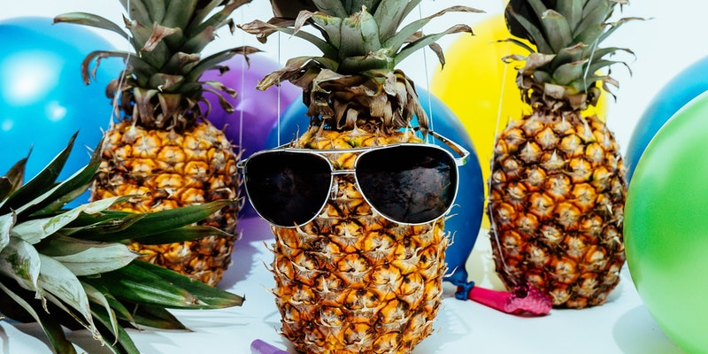 Multiple balloons in different colors, pineapples wearing party hats, and sunglasses.