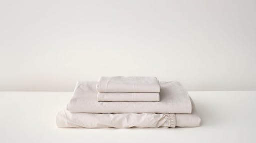 Folded percale sheets and pillowcases in sand