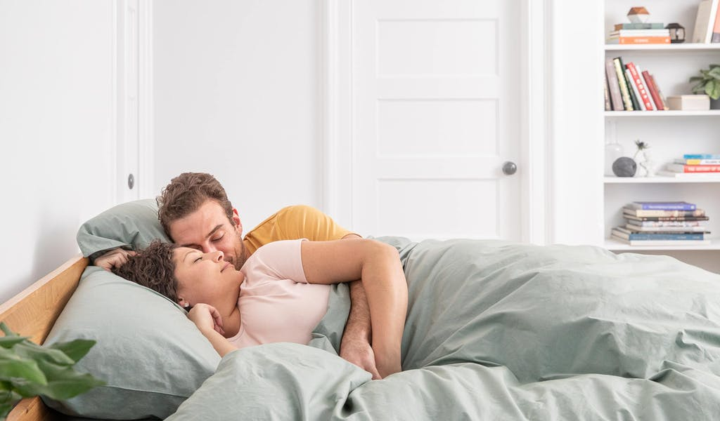 Couple lying in bed, on a Tuft & Needle Hybrid mattress