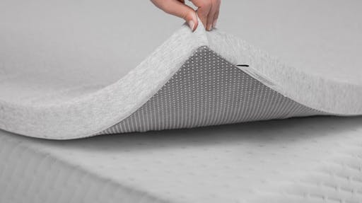 Person holding up the corner of the foam mattress topper