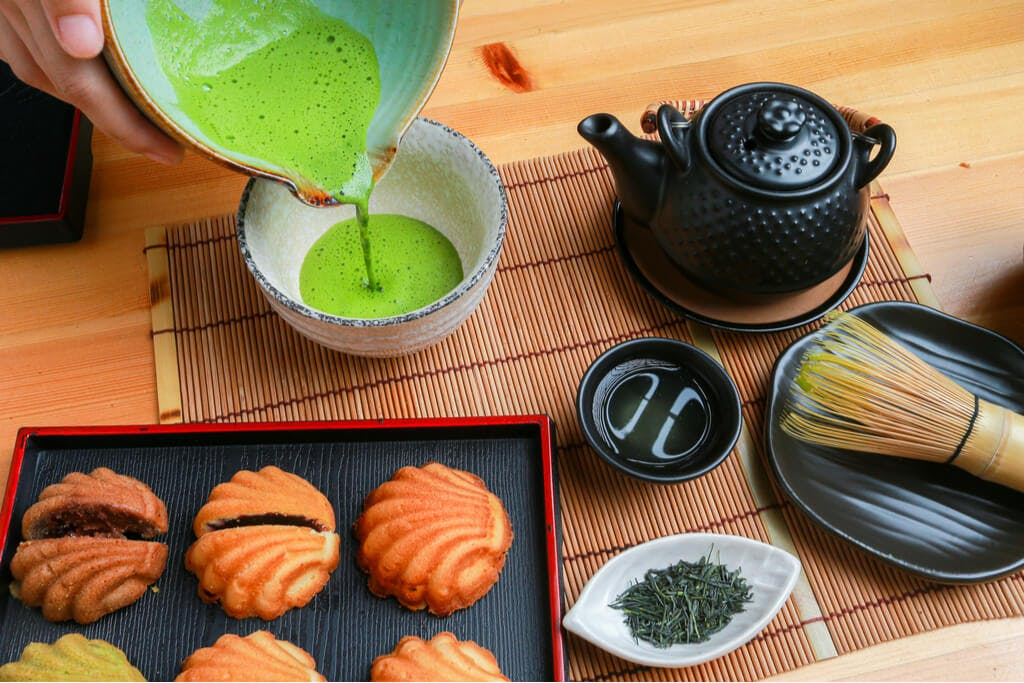 A hand pours matcha into a bowl that is between a teapot, leaves, manju, and a whisk