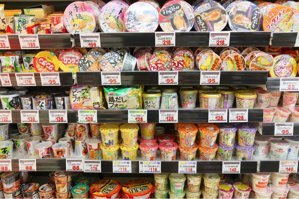 A large shelf of Japanese cup ramen in a supermarket with many different prices displayed in front of each type