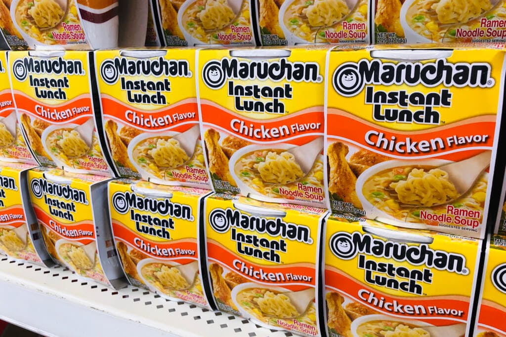A row of Maruchan chicken flavored cup noodle on a shelf in a grocery store