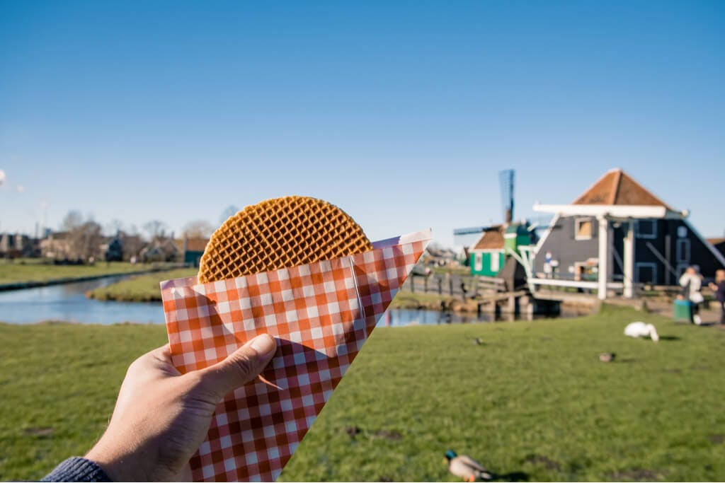 A hand holding a Stroopwafel in front of a windmill and a hut at a park.