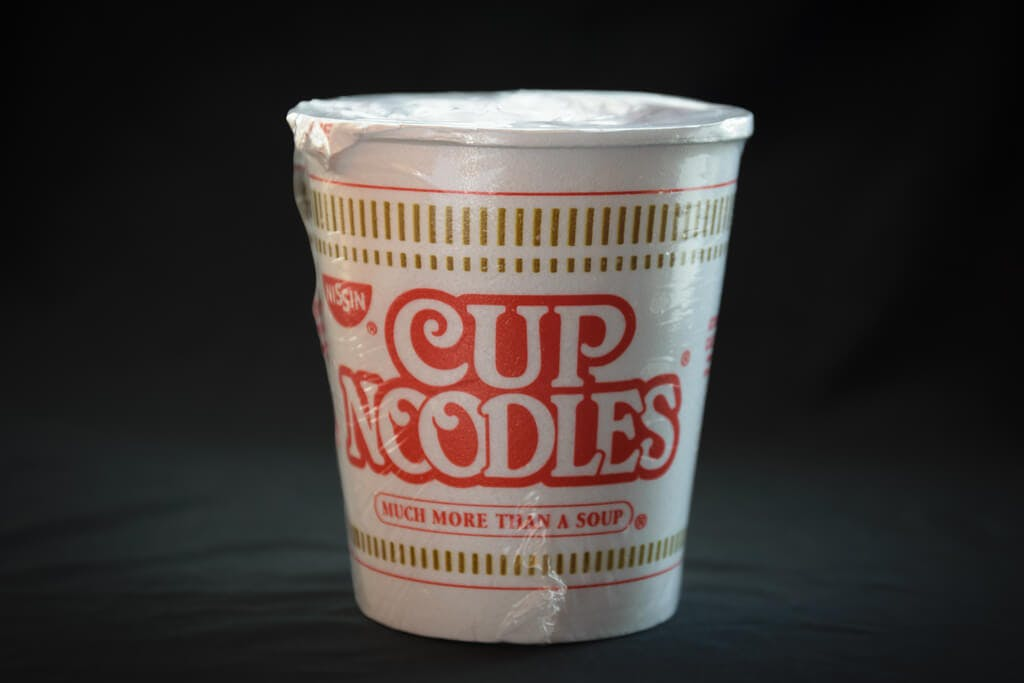 A cup of the original cup noodles on a black background still in the packaging