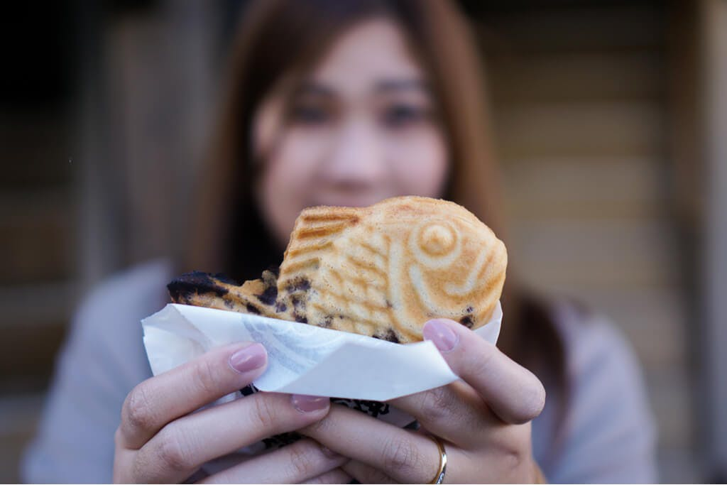 A young Japanese woman holds a taiyaki with chocolate chips in it.