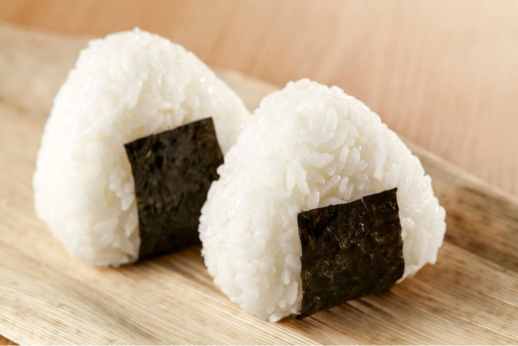 Two plain rice balls with black seaweed wrapped around them on a wooden tray on a table