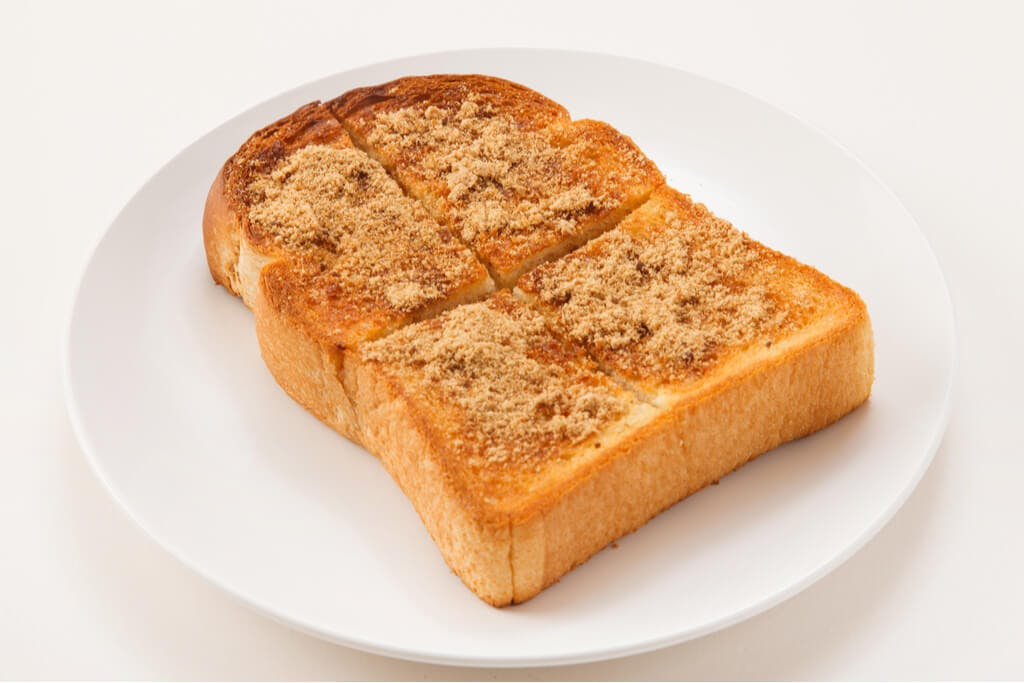 Japanese milk bread toast with kinako powder on a plate on a white table