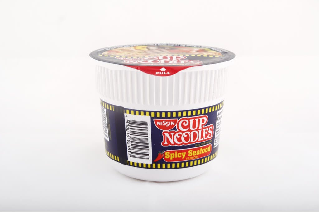 A cup of Nissin Cup Noodles Spicy Seafood flavor in front of a white background