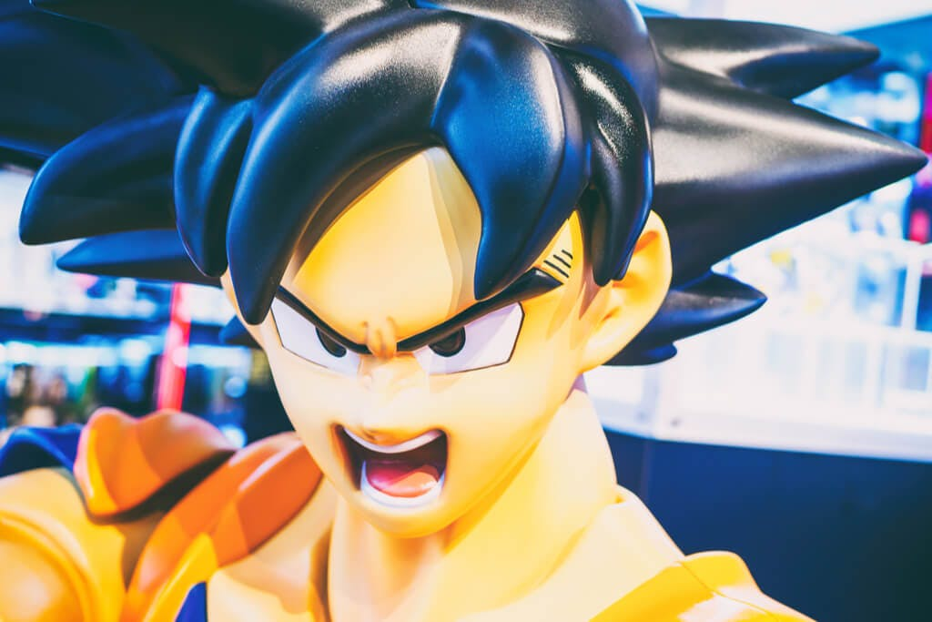 A Dragon Ball Z figure of Goku in a shop with a background of lights.