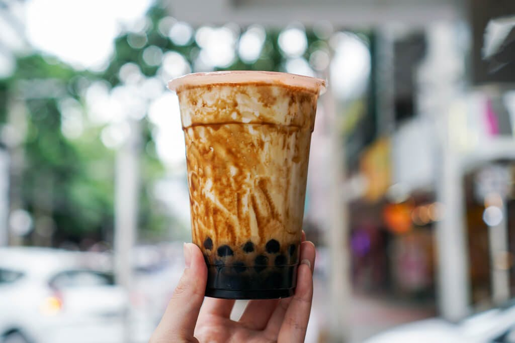 A hand holds brown sugar syrup bubble tea up on a sidewalk in front of cars and stores