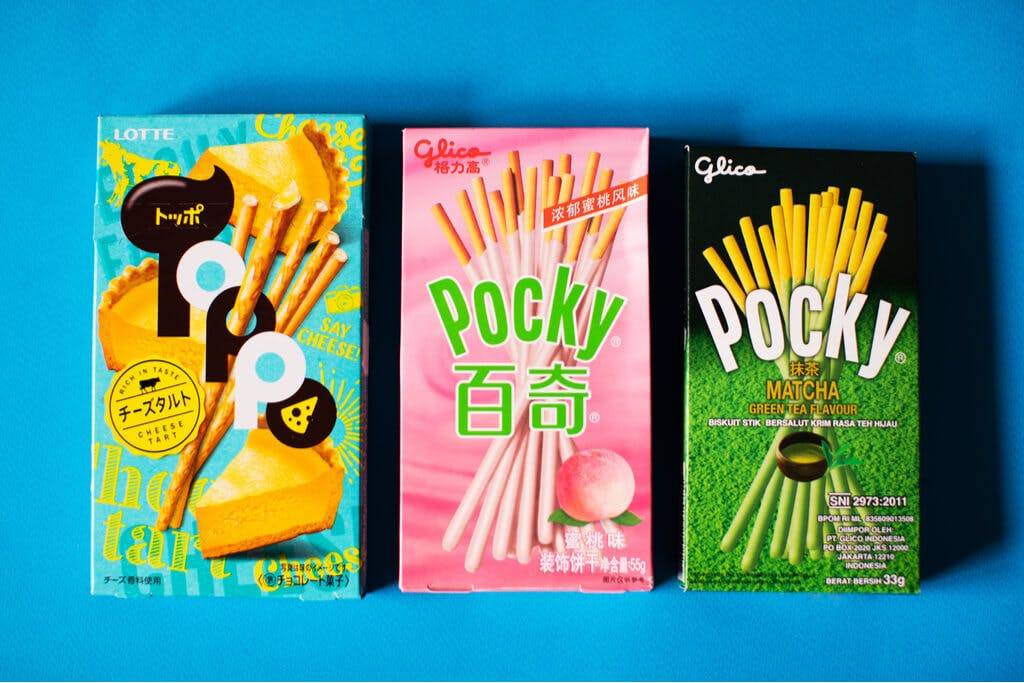 A box of cheesecake Toppo next to two boxes of peach and green tea Pocky.
