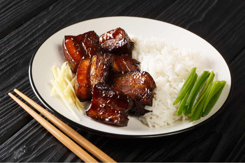 Okinawa braised pork in a black sugar sauce with rice and onions on a white plate next to chopsticks on a black table