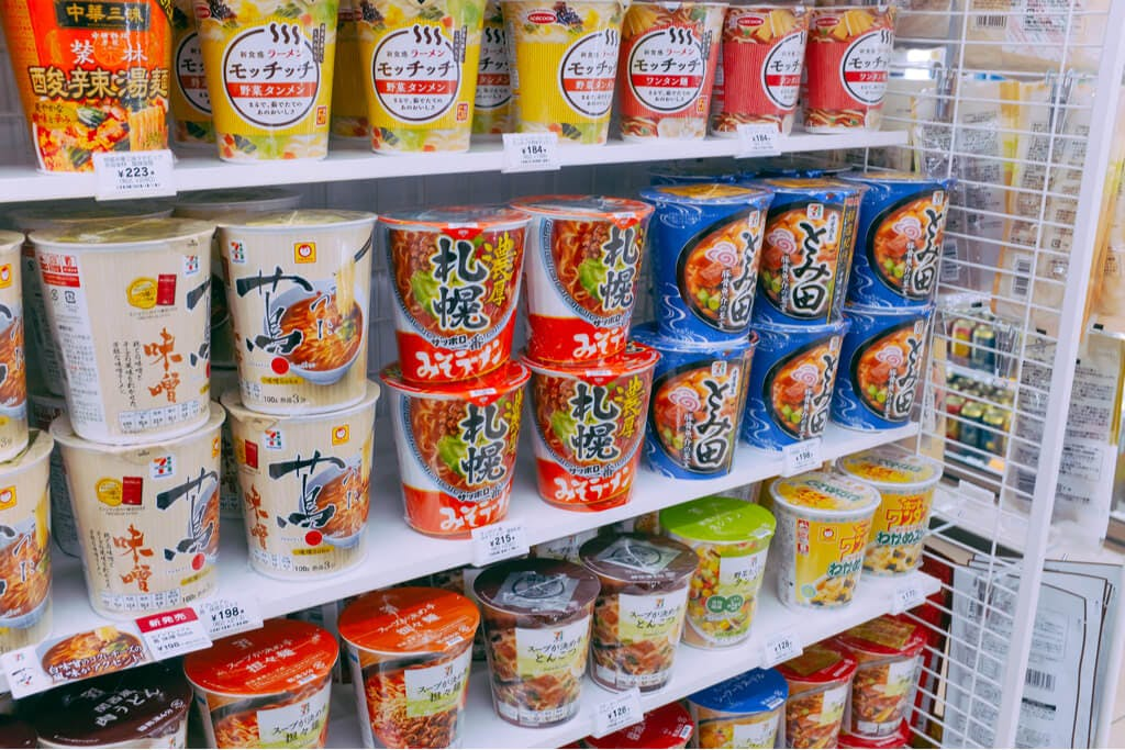 Sapporo Noko Miso, one of the best cup ramen, on a white shelf in a convenience store among other ramen cups