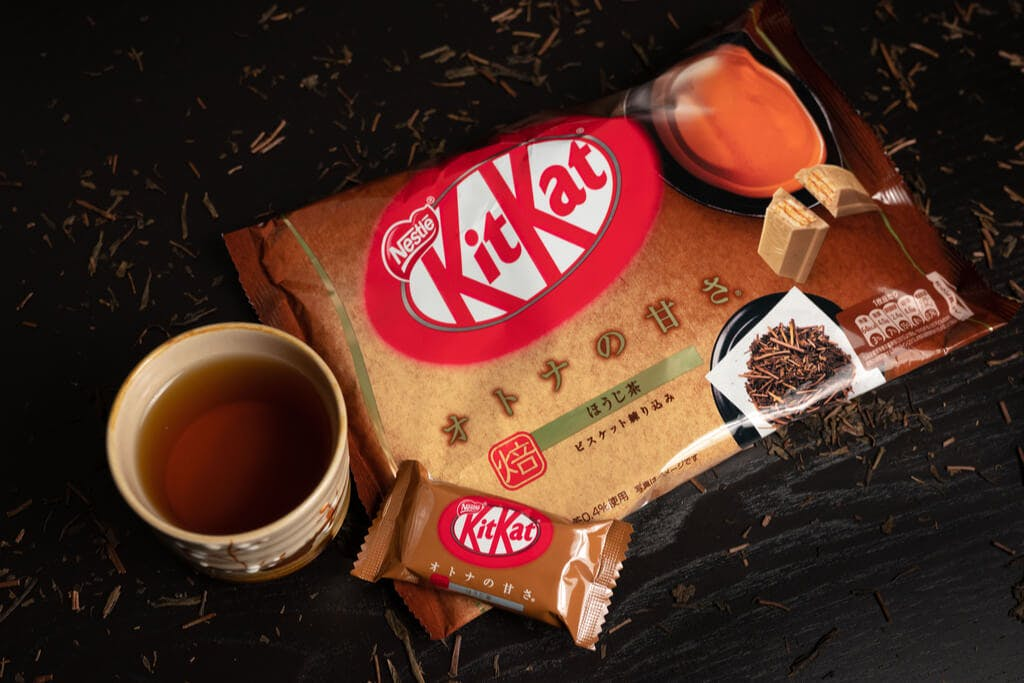 Roasted green tea Kit Kats next to a cup of roasted green tea on a black table with roasted green tea leaves and stems