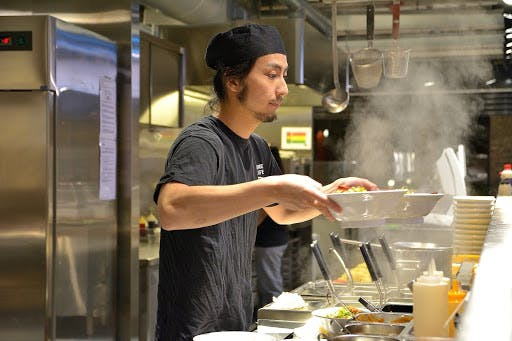 A Japanese chef serves piping hot bowls of ramen to his customers