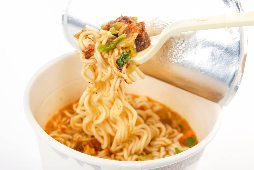 A cup noodle version of Tantanmen, with the lid open with some hanging from a plastic fork