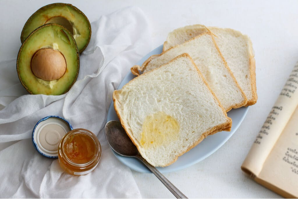 Japanese milk bread with some orange jam on it between an avocado and a book