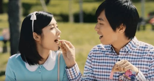 A couple takes smaller bites of gummy candy from the famous long long man commerical.