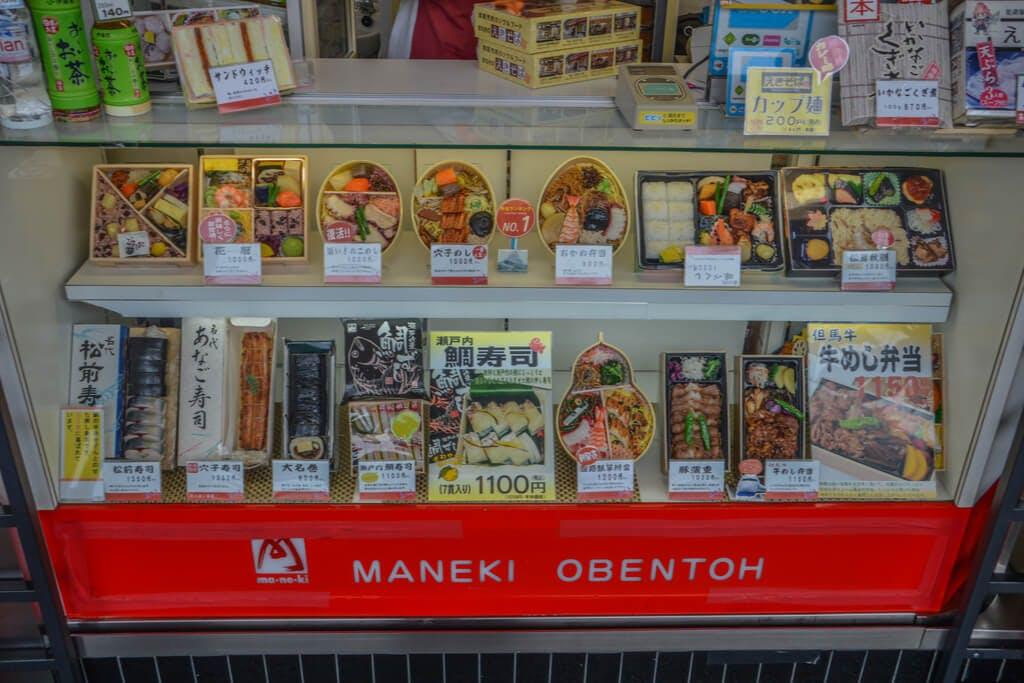 A display of bentos at a bento shop called Maneki Obentoh at a station with many types of ekiben.