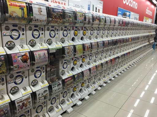 A wall of gashsapon Japanese vending machines containing mystery toy capsules.