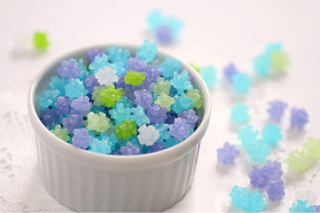 A white cup filled with blue, green, purple, and white konpeito with konpeito strewn on the table next to it