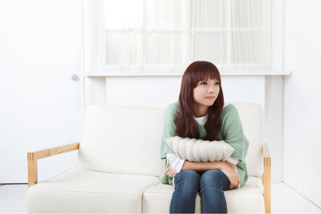 A Japanese woman sitting and waiting on a white couch while holding a white pillow in a white room