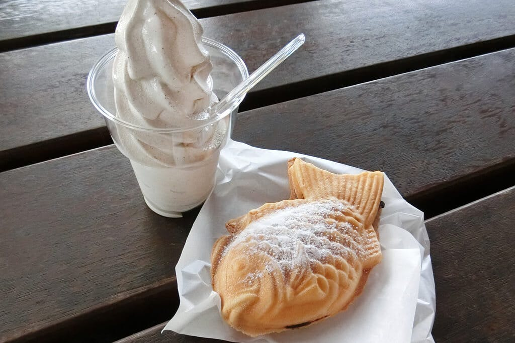 A taiyaki next to a cup of soft-serve vanilla ice cream