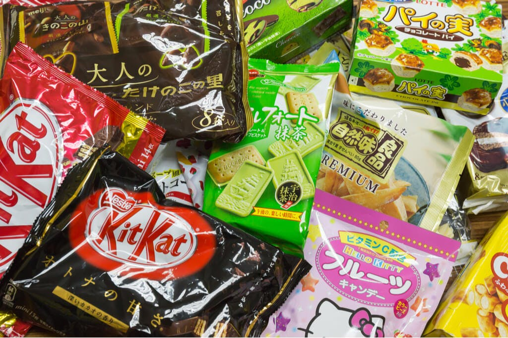 A pile of Japanese snacks including Kit Kats, fruit candy, Alforts, and pie seeds