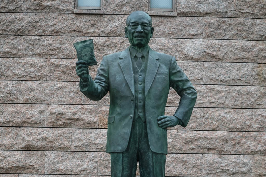 A green statue of the Inventor of instant and cup noodles Momofuku Ando in front of a gray wall.