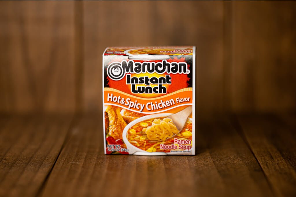 A package of Maruchan Instant Lunch Hot & Spicy Chicken flavor cup noodles on a wood surface in front of a wood wall
