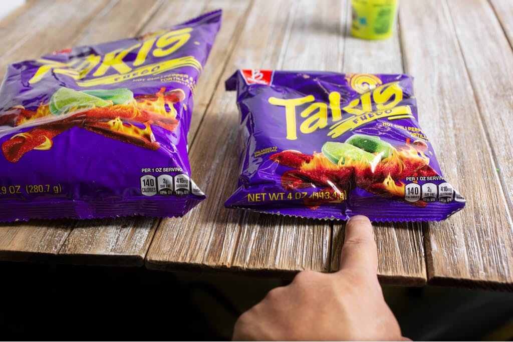 A hand pointing at two bags of the mexican snack Takis.