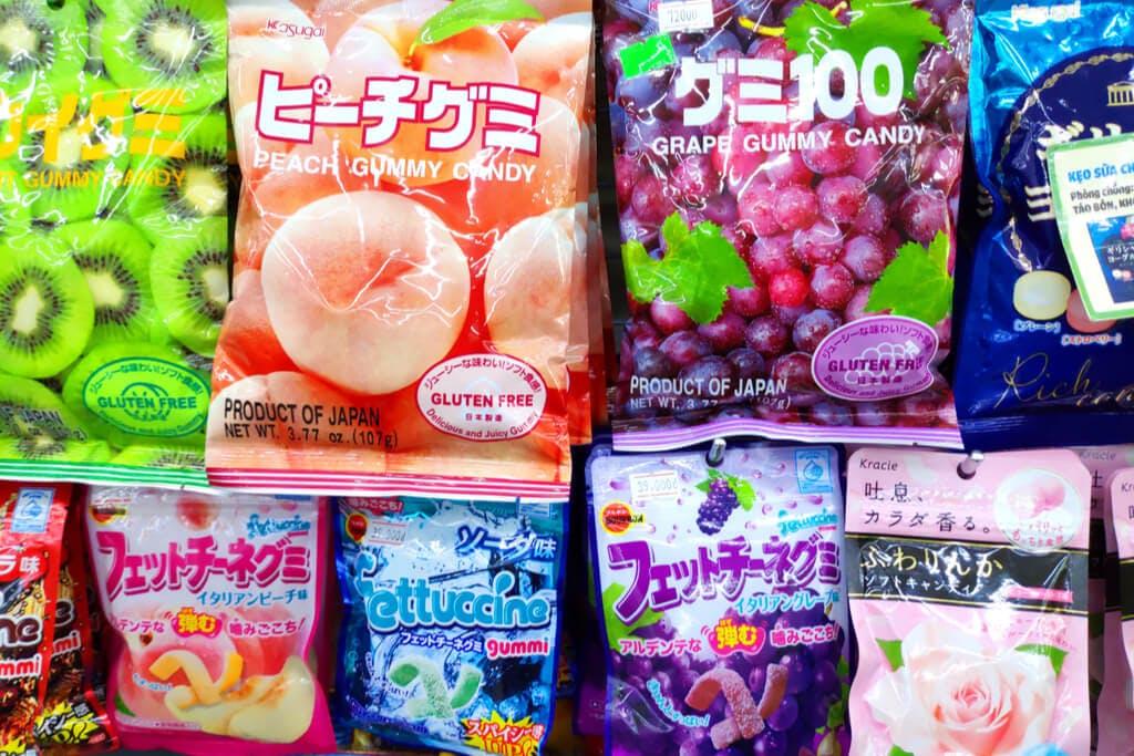 Several bags of Japanese gummy candy hanging in a store