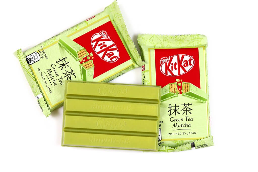 A block of Japanese green tea Kit Kats on a white background with two packages of them next to it.