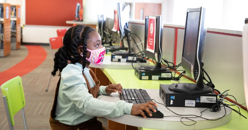 Girl wearing a mask and using a library computer