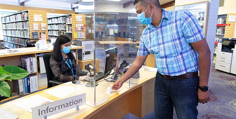 Customer registering for a library card with staff.
