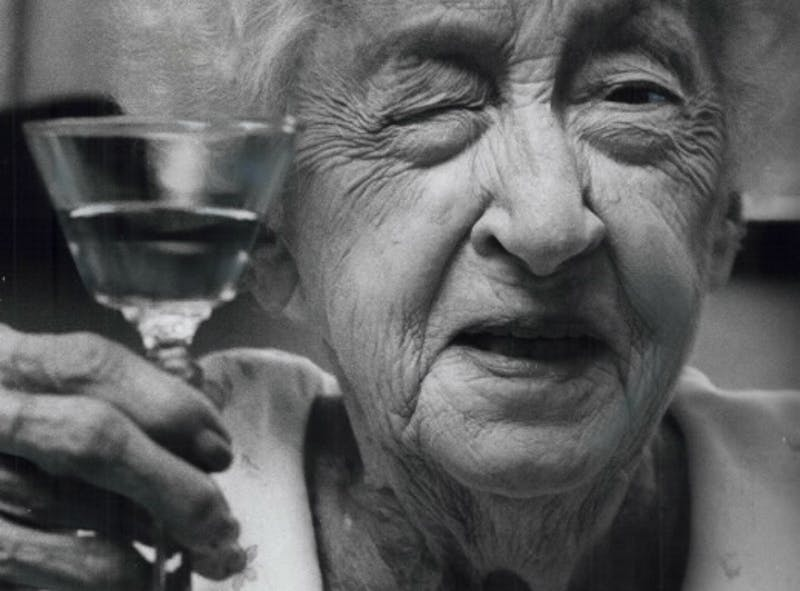 An elderly woman holding up a sherry glass and winking.