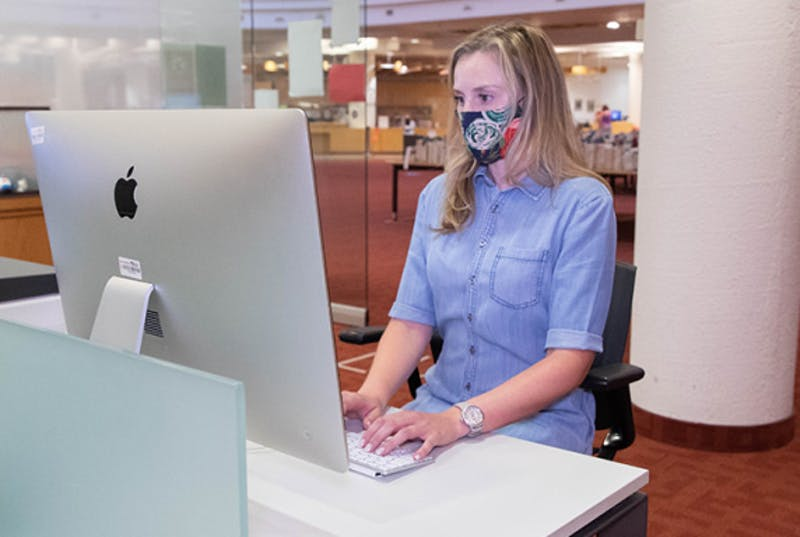 Woman in mask looking at iMac screen
