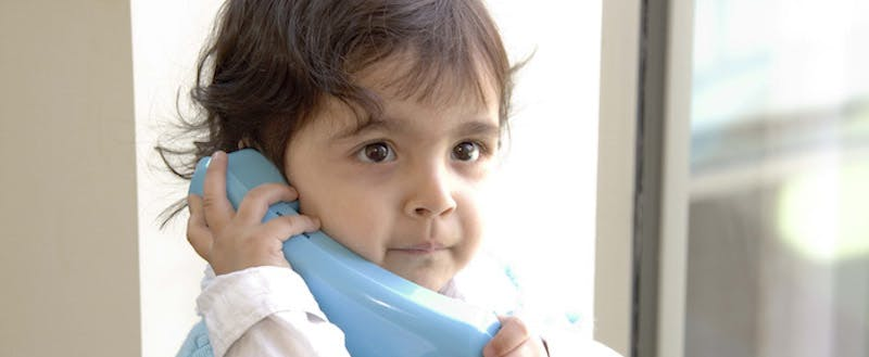 Child holding phone receiver to ear