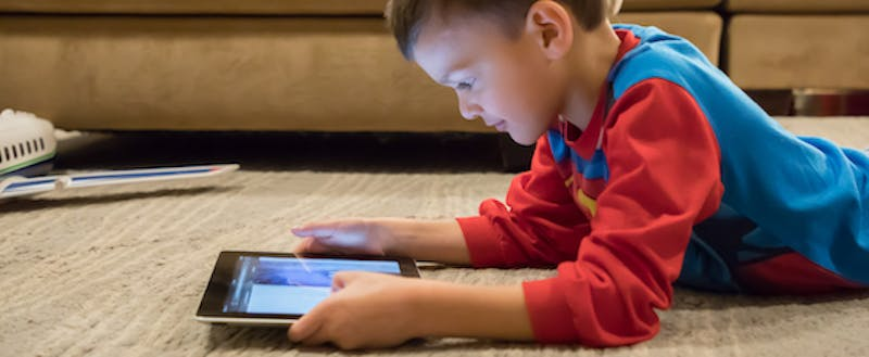 A kid reads on a tablet at home