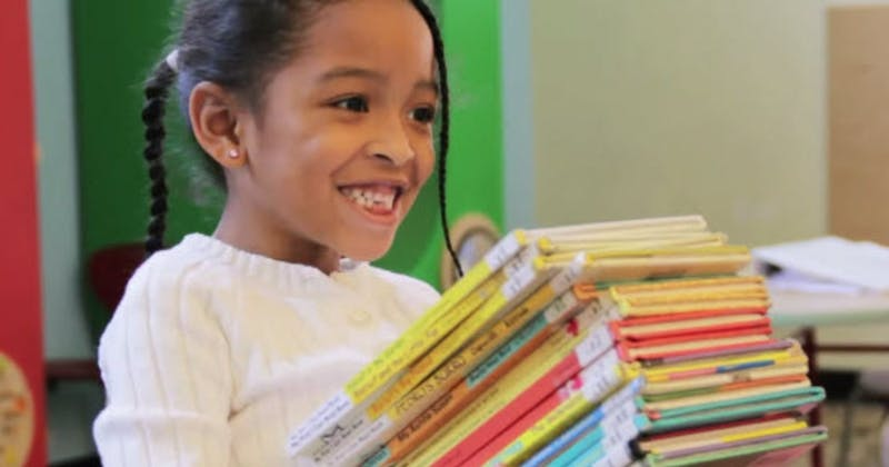 Smiling child carrying a stack of books