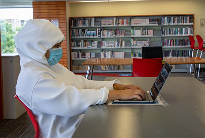 Teen on a laptop wearing a mask