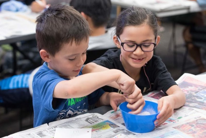 Two kids mixing science experiment in a bowl