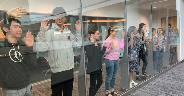 Teens pose through a glass wall, 2019