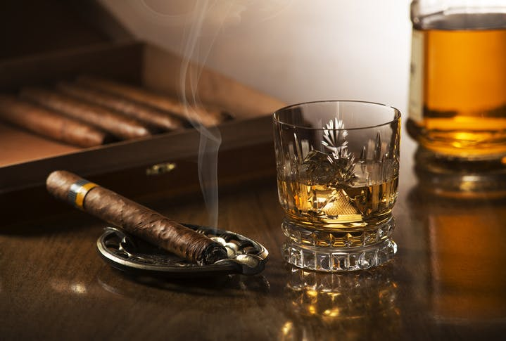 Image shows a smoking cigar on an ash tray beside a crystal glass containing whisky
