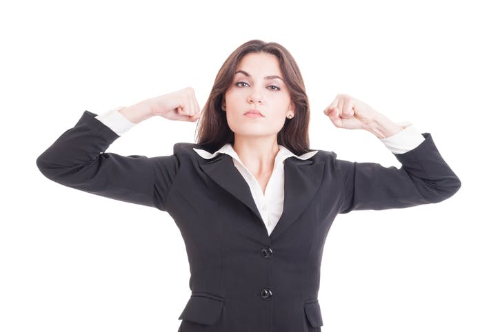 Image shows woman in business suit with both arms raised and hands clenched