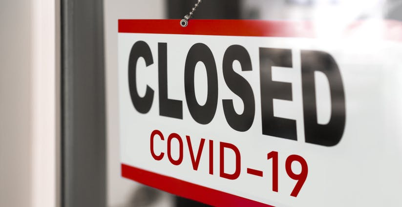 Image shows a rectangular sign on a glass door with the words 'CLOSED' in red and 'Covid 19' in black underneath