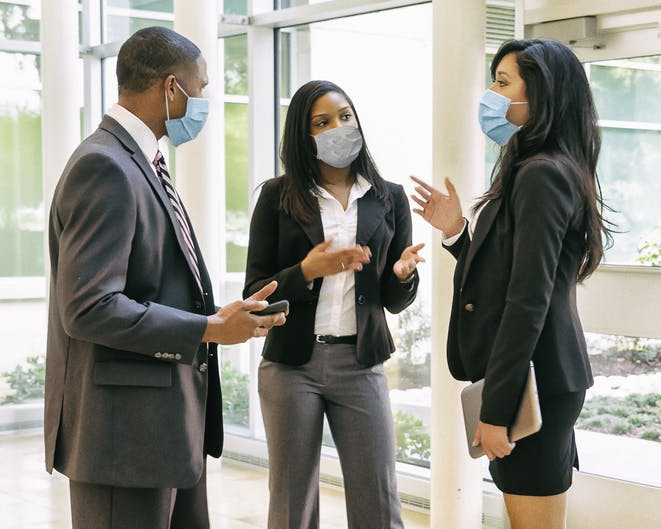 Image shows one man and two women in masks holding a meeting