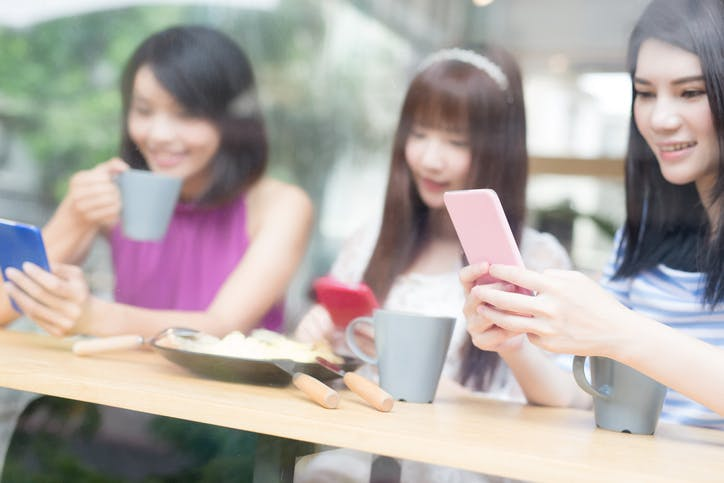 Three young women play on their mobiles while sitting in a coffee shop