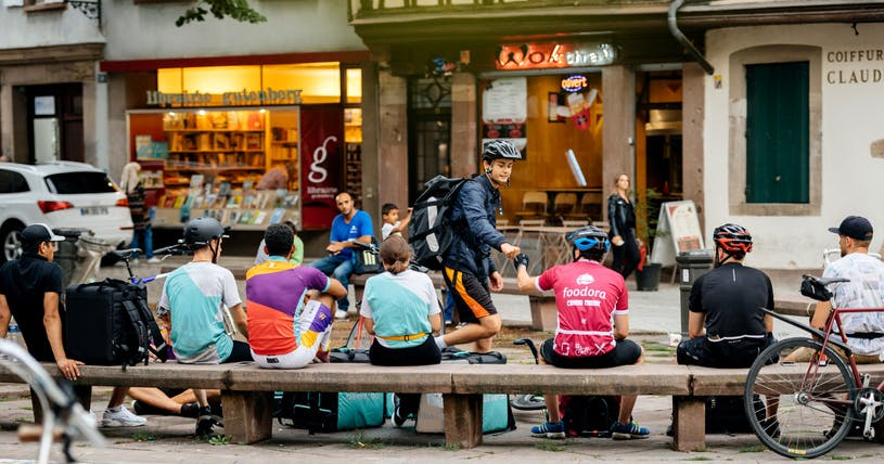 A bunch of Deliveroo riders have a rest on a wooden bench outside a coffee shop